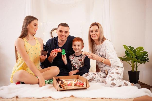 Pai, mãe, filha e filho comem deliciosos bolos e doces no quarto