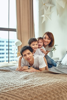 Pai, mãe, filho e filha posando em casa