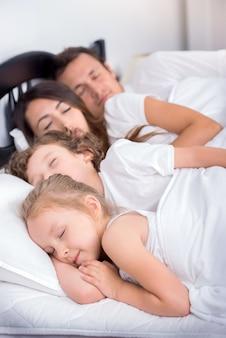 Pai, mãe, menino e menina dormindo na cama.
