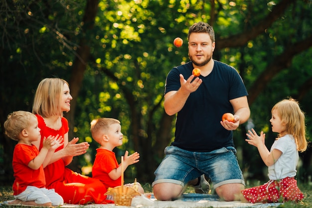 Pai malabarismo laranjas na frente de sua família
