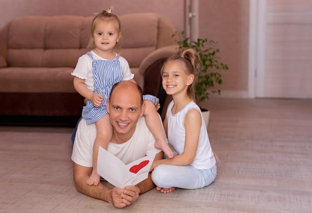 Pai mantém um cartão de filhas alegres no dia dos pais durante as férias em casa