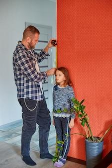 Pai mede a altura da filha contra a parede em casa
