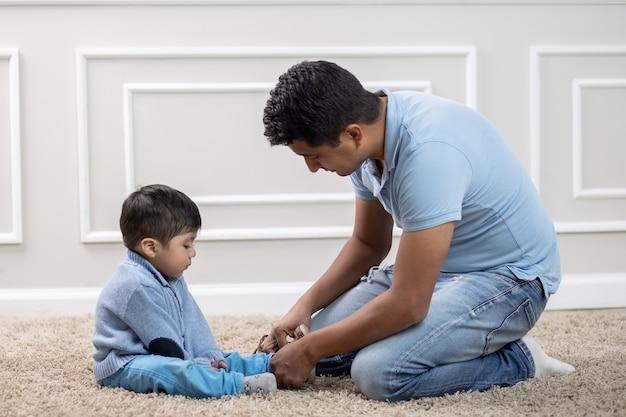 Pai mexicano apertando sapatos para filho