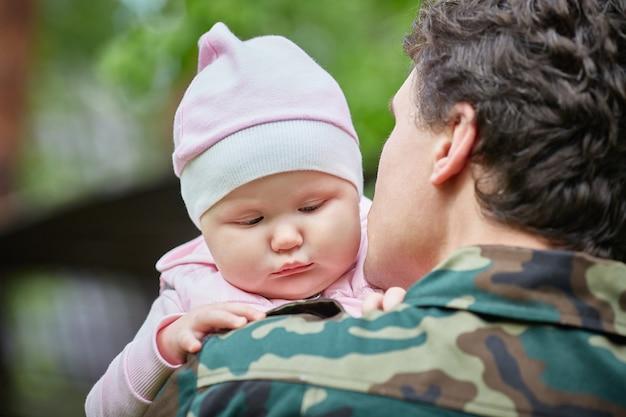 Pai militar vai para a guerra e segura uma filha triste de um ano de idade nos braços.
