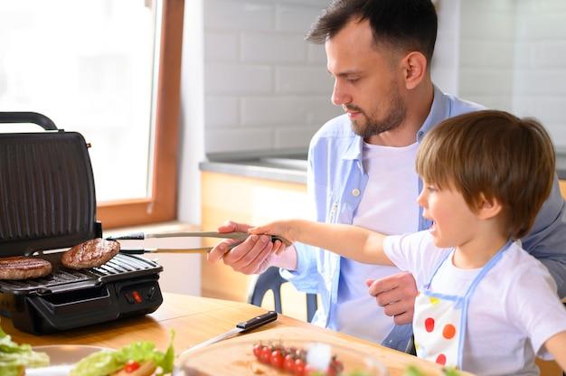 Pai monoparental e criança cozinhar hambúrgueres