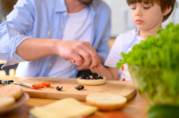 Pai monoparental e criança fazendo sanduíches
