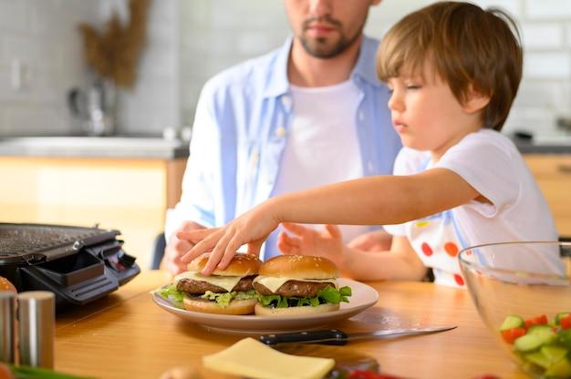 Pai monoparental e criança organizando os hambúrgueres