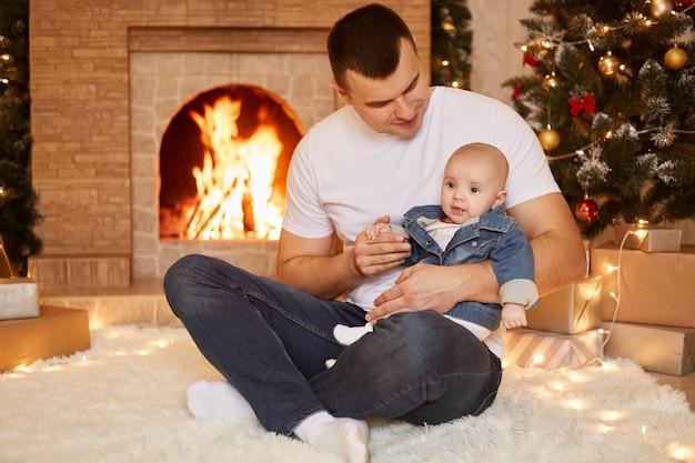 Pai moreno adulto jovem vestindo jeans e camiseta casual branca segurando a filha pequena nas mãos, posando em casa perto da lareira e da árvore de natal, passando as férias de inverno com a família.