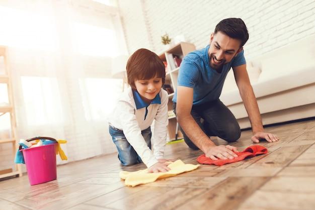 Pai mostra ao filho como limpar a casa.