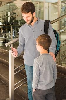 Pai mostrando algo para seu filho no celular