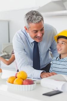 Pai mostrando o filho seus planos quando ele está usando capacete amarelo