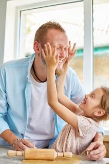 Pai mostrando sua filha como rolar a massa para biscoitos