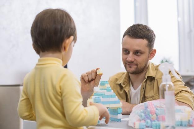 Pai mostrando um pedaço de lego para seu filho