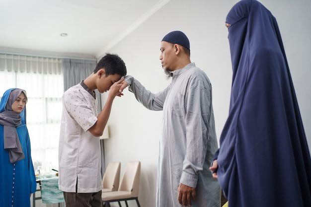 Pai muçulmano asiático apertar a mão em idul fitri eid mubarak