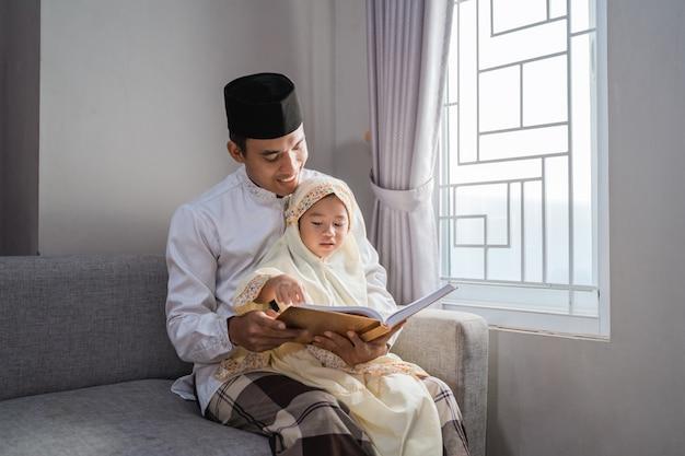 Pai muçulmano leu alcorão com sua filha