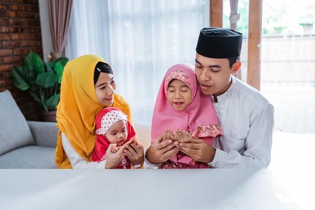 Pai muçulmano, mãe e filha rezando juntos