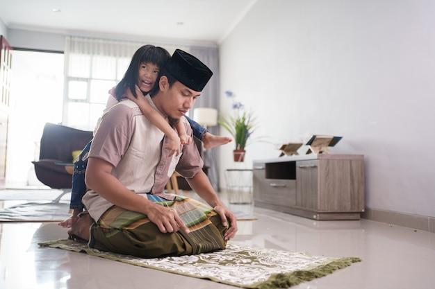 Pai muçulmano sendo incomodado por sua filha enquanto orava em casa