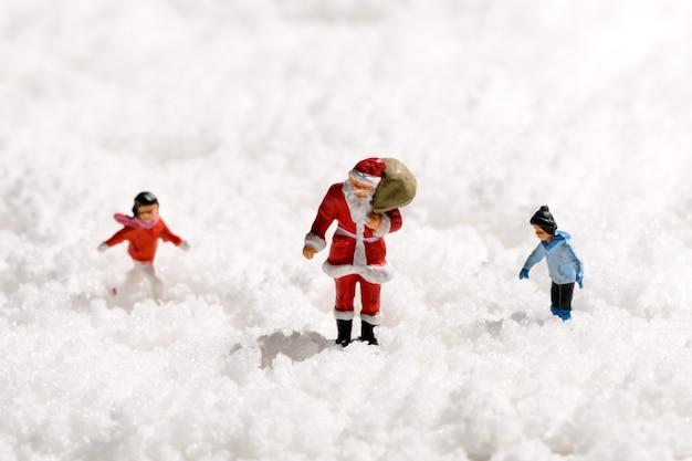Pai natal em miniatura ou papai noel carregando um saco de presentes