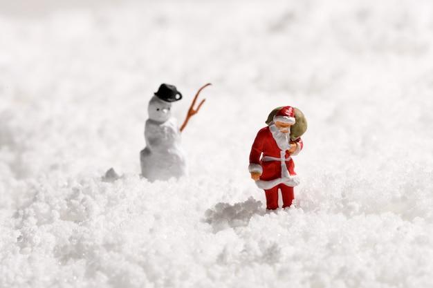 Pai natal ou papai noel e um boneco de neve na neve do inverno