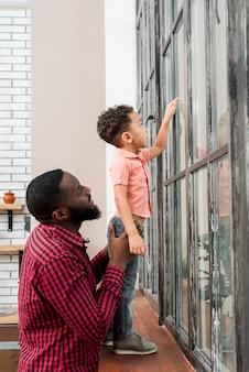 Pai negro e filho a olhar para a janela apontando para fora