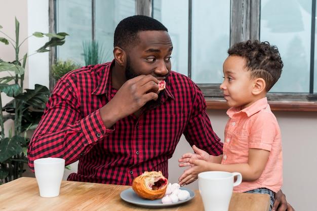 Pai negro e filho tomando café da manhã