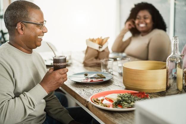 Pai negro feliz bebendo erva-mate durante o almoço em casa - foco principal na mão