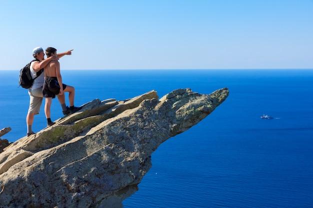 Pai no topo de uma montanha mostra filho navio longe no mar