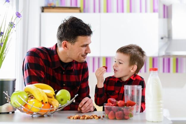 Pai novo e filho bonito sentado junto à mesa da cozinha cheia de frutas frescas. rapaz está comendo morangos.