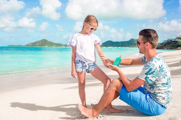Pai novo que aplica o creme do sol ao nariz da filha na praia.