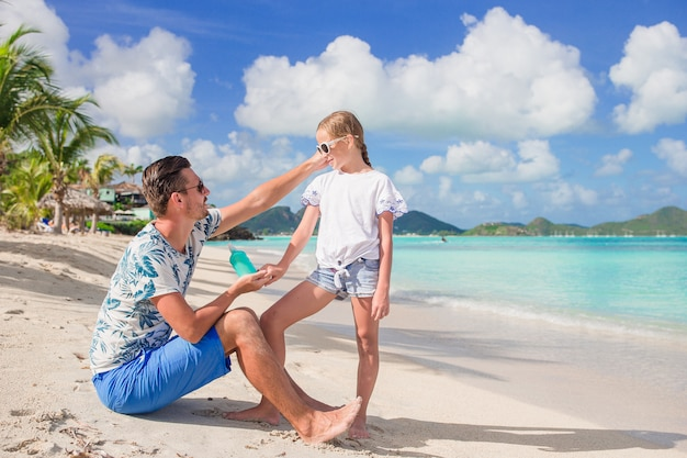 Pai novo que aplica o protetor solar ao nariz da filha na praia. proteção solar