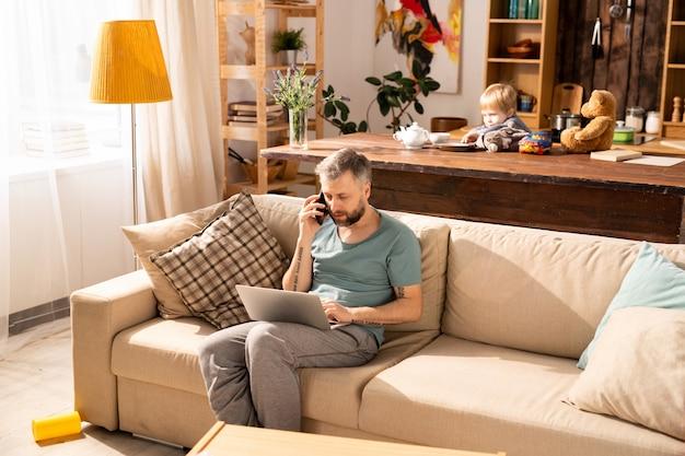 Pai ocupado trabalhando em casa enquanto filho sendo entediado