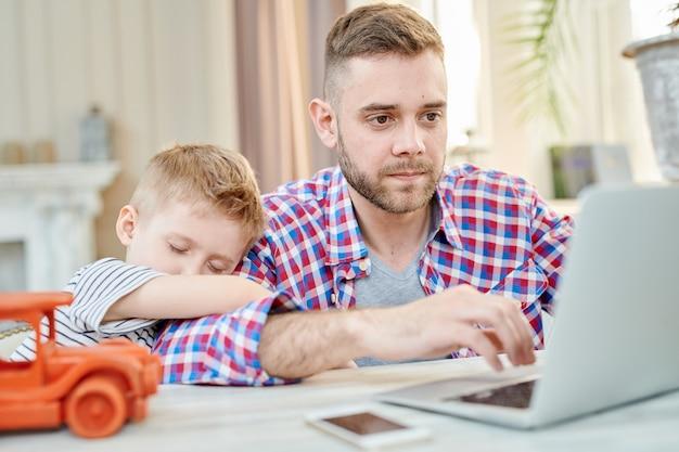 Pai ocupado trabalhando no laptop