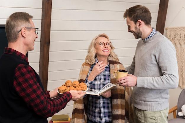 Pai oferecendo bolos para filho e mãe