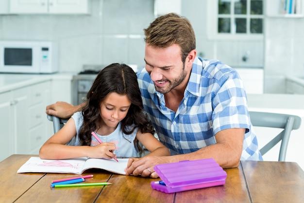 Pai olhando a filha enquanto desenha no livro