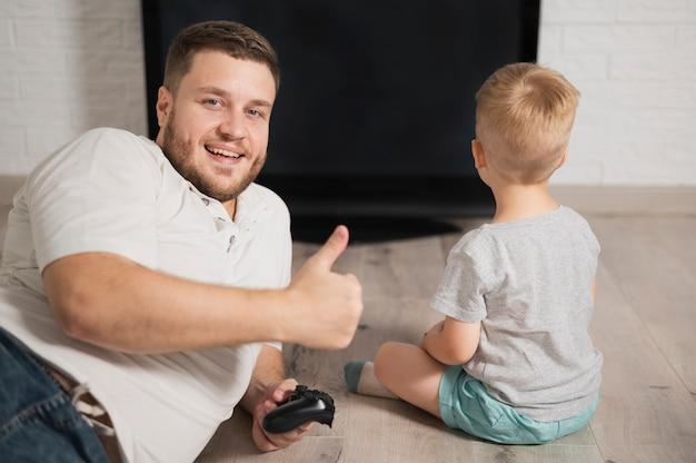 Pai olhando para a câmera enquanto fica ao lado de seu filho