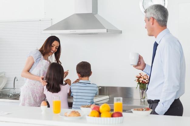 Pai olhando para a família cozinhar na cozinha