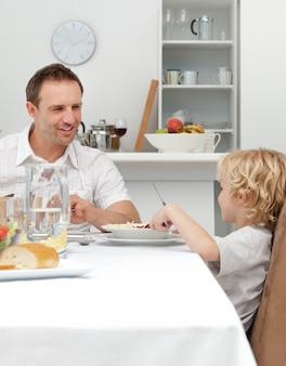 Pai orgulhoso falando com seu filho ao comer macarrão juntos