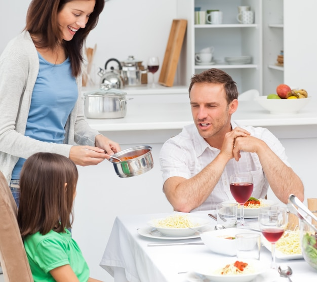 Pai orgulhoso falando com sua filha enquanto a mãe lhe dá o molho de macarrão