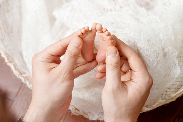 Pai ou médico massageando o pé do bebê pequeno. pai, segurando suavemente as pernas de uma criança recém-nascida nas mãos. família feliz .