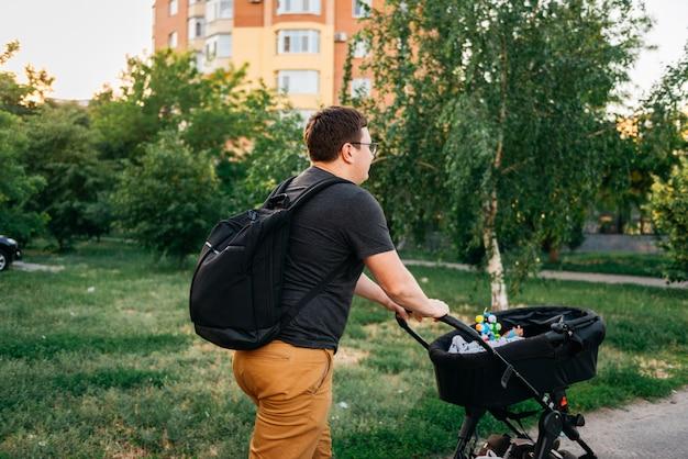 Pai pai com carrinho de carrinho de bebê recém-nascido fora durante o pôr do sol de noite de verão