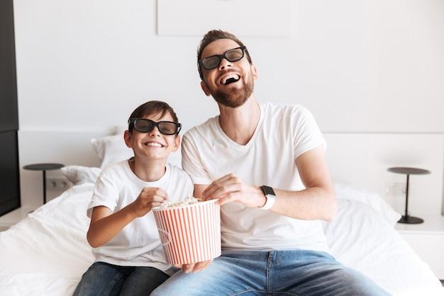 Pai pai homem com seu filho assistindo tv comendo pipoca usando óculos 3d.