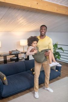 Pai. pai jovem e forte de pele escura e sorridente em roupas casuais, segurando a filhinha encaracolada nos braços em casa