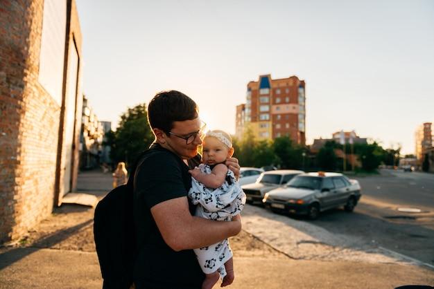 Pai, pai, segurando, bebê recém-nascido menina infantil, ligado, mãos, ao ar livre, verão, pôr do sol, noite