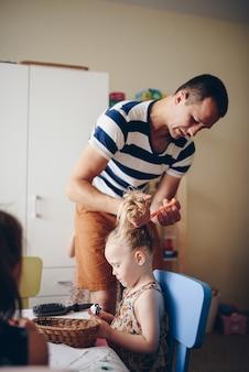 Pai penteia a filha e faz o cabelo dela.