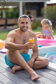 Pai perto da piscina. pai barbudo e alegre sentado perto da piscina com sua esposa e filha