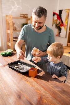 Pai positivo e filho colocando biscoitos na caixa de presente
