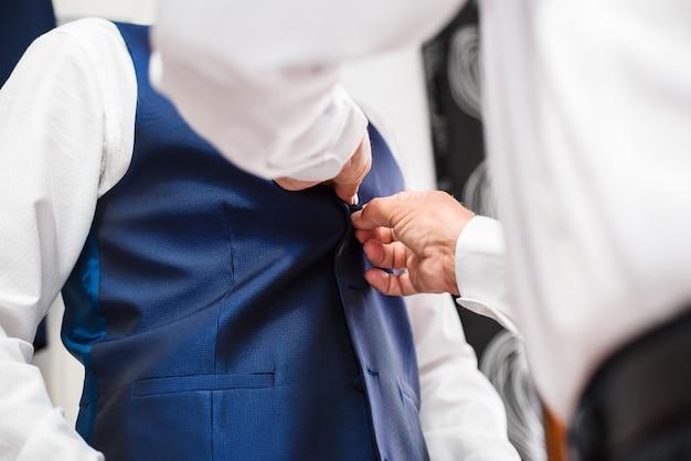 Pai que ajuda o noivo que prepara-se na manhã para a cerimônia de casamento.