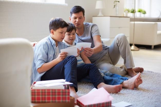 Pai que mostra fotos aos seus filhos