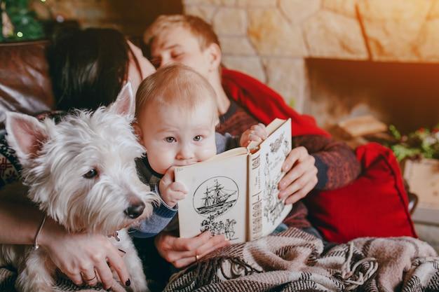Pai que prende um livro onde o bebê está se inclinando