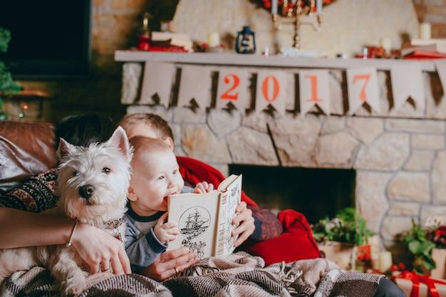 Pai que prende um livro que seu bebê está olhando e tocando